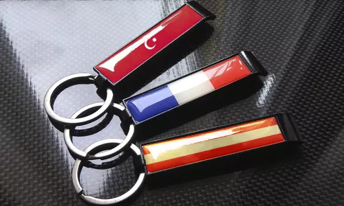 three bottle opener keychains with flags